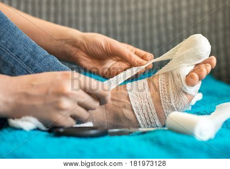 Woman Bandaging Her Injured Leg On Sofa At Home.