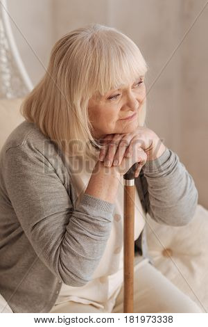 I wish I were young again. Nice dreamy elderly woman holding a walking stick and thinking about her past while resting at home