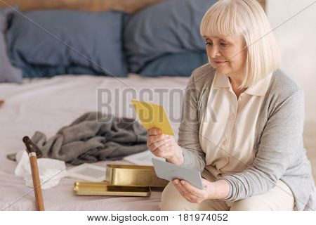 My memories. Sad cheerless senior woman looking at the old postcard and feeling nostalgic while turning over old letters