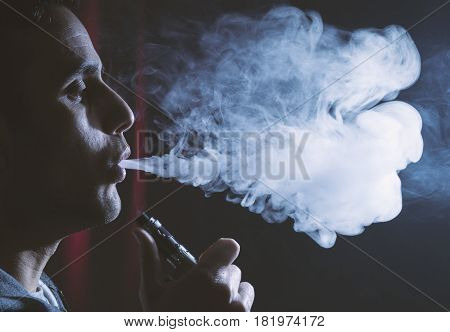 Young Person Holding Electronic Cigarette Or E Cig And Vaping Clouds.