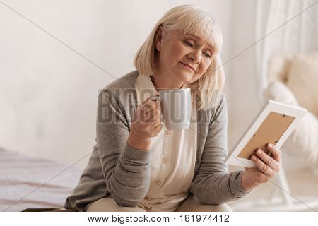 I miss you. Sad thoughtful elderly woman holding a cup and having tea while looking at the photograph of her husband