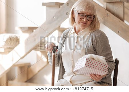 His present. Nice depressed senior woman sitting on the chair and looking at the gift box while holding a walking stick