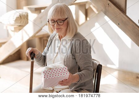 He gave it to me. Sad elderly cheerless woman looking at the present and thinking about her husband while sitting on the chair