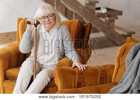 Being alone at home. Sad moody distressed woman sitting in the armchair and closing her eyes while feeling lonely