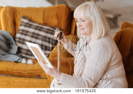 My dear husband. Unhappy gloomy elderly woman holding a photograph and looking at it while being in grief about her husband