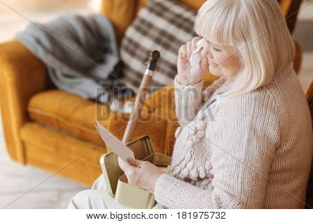 I will never forget. Sad cheerless unhappy woman holding a letter and crying while having nostalgic memories of her past
