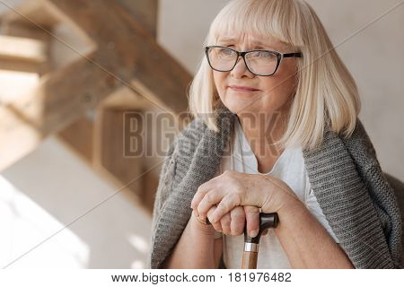 I am already old. Unhappy thoughtful elderly woman holding a walking stick and leaning on it while thinking about her life