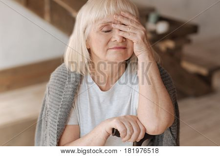 I am so exhausted. Sad pleasant elderly woman closing her eyes and touching her forehead while feeling tired