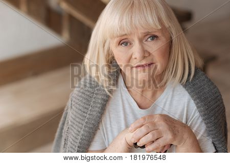 Period of depression. Portrait of an upset depressed aged woman holding her stick and looking at you while being unhappy