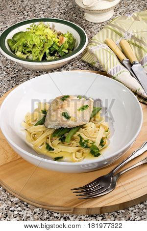 steamed mackerel with butter lemon sauce tagliatelle and coriander on a plate