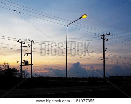 Silhouette of electric poles and cables over sunrise sky background. Energy and technology concept.