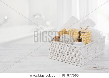 Box with spa products on wood over blurred bathroom interior
