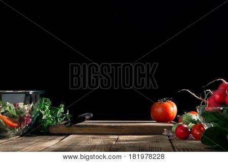 Kitchen wooden board with free place on a wooden table with fresh vegetables for cooking healthy food