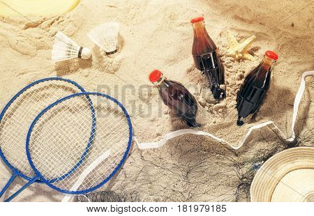 Summer background. Three bottles of cool drink with items for beach entertainment on sand top view