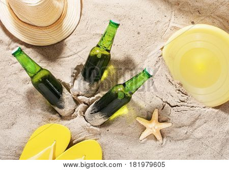 Cold lager beer with beach items on sand top view. Summer background