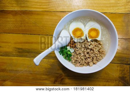 Minced pork congee with egg fresh ginger and coriander in white cup and spoon over the wood table.