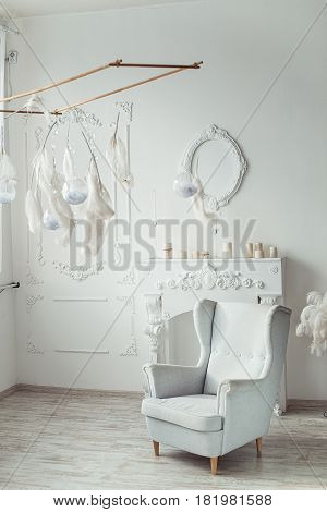 white entrance area interior with fake Camino, vintage chair, decoration feather.