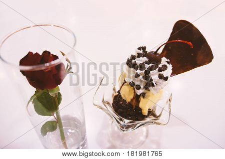 Chocolate and vanilla ice cream sundae isolated on white background with copy space. Topping are whip cream chocolate chip chocolate waffle and red rose. Add classic chrome film simulation. For food.