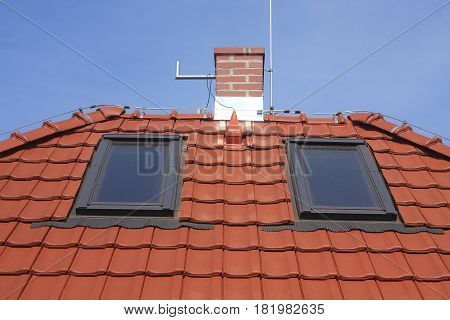 Roof windows red clay tiles chimney and lightning
