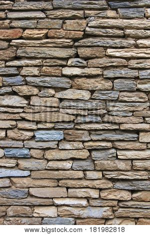 Natural grunge brown stone wall background and texture random pattern exterior decoration.