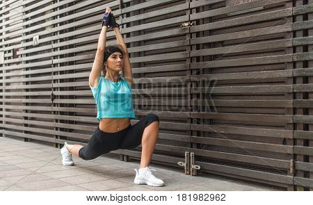 Fit young woman doing yoga stretching exercise, low lunge asana Anjaneyasana pose, outdoors