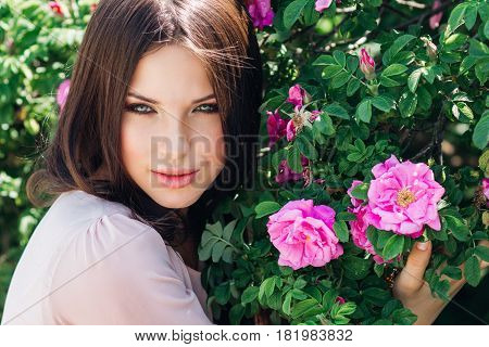 Beautiful young woman with long curly hair posing near roses in a garden outdoors. The concept of perfume advertising.