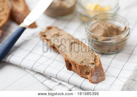 Bread with veal and rabbit pate with butter on a textile background.
