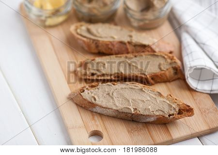 Bread with veal and rabbit pate with butter on a bamboo board.