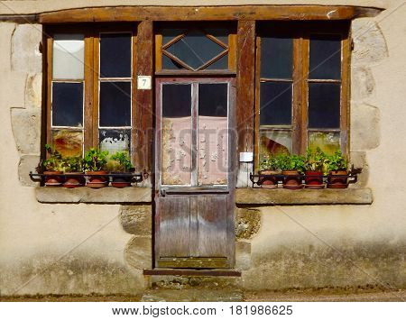 French house front with pots of geraniums on windowsills