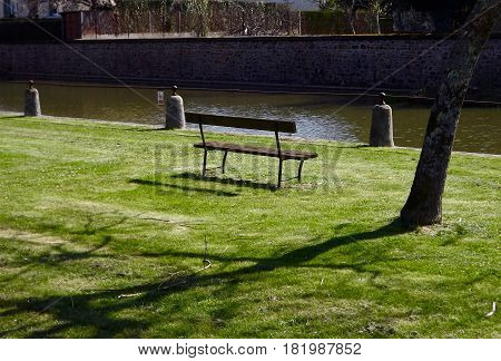 Park bench by waterside in rural France