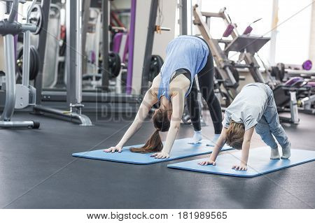 mother and child doing fun yoga session at gym