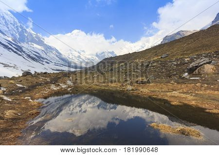Himalaya Annapurna snow mountain range with reflection on pond on the way to Annapurna base camp famous trekking trail in Nepal.