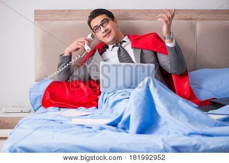 Super hero businesswoman working in bed