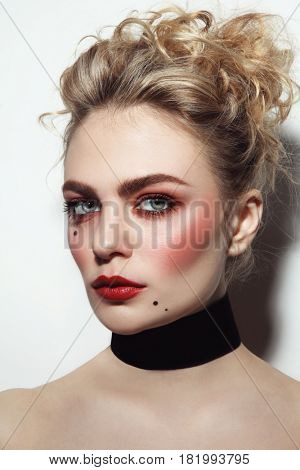Portrait of young beautiful blonde girl with vintage style make-up and hairdo