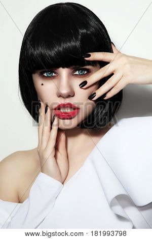 Portrait of young beautiful woman with bob haircut, smoky eyes make-up and stylish black manicure