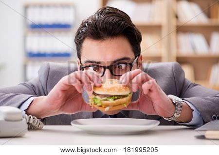 Hungry funny businessman eating junk food sandwich