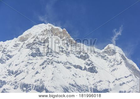 Himalaya Annapurna South snow mountain peak in blue sky view from Annapurna base camp famous trekking destination in Nepal.