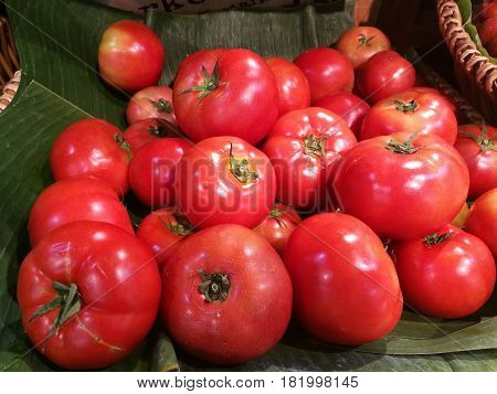 Fresh organic tomato stand out among many tomato on banana leave with blur background in basket in supermarket. Heap of tomato close-up