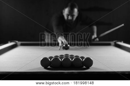 monochrome photo of young man playing billiards