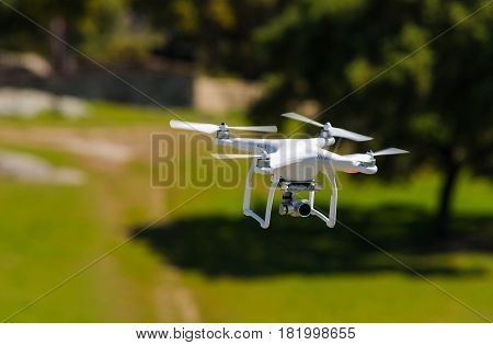 white flying drone armed with camera. Drone in nature