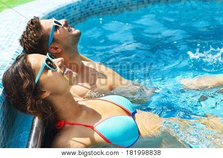 Young couple are relaxing in swimming pool. Summer vacation concept