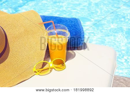 Swimming pool orange juice beach towel sunglasses on sun bed. Summer vacation concept