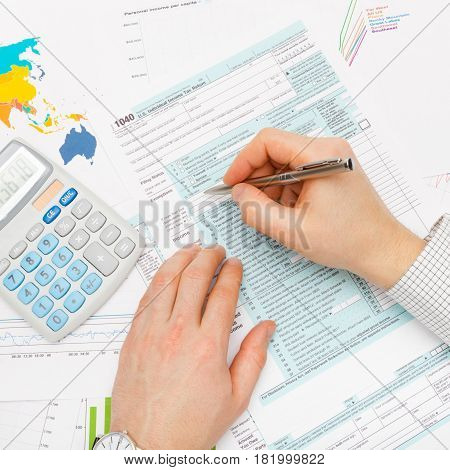 Business Man Filling Out 1040 Us Tax Form With Calculator Next To His Left Hand