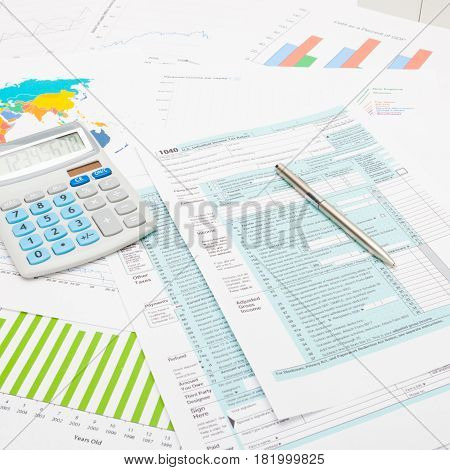 Calculator And Pen Over Us 1040 Tax Form And Some Financial Charts