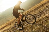 Male in sportswear riding on bike off road pn background of plain in sun light. poster
