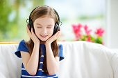 Cute little girl wearing huge wireless headphones. Pretty child listening to the music. Schoolgirl having fun listening to kid's songs at home. Home technology and music concept. poster