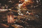 Old cracked mossy tombstone on graveyard with orthodox crosses above tombs in blurred background on moody autumn morning with copy space for your text message poster
