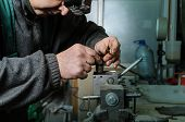 Mechanics repairing a diesel injector. Man disassemble a injector pinched in a vise. poster
