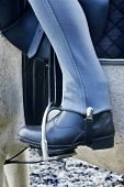 Woman's leg with blue jodhpurs and black riding boots with foot in stirrup poster