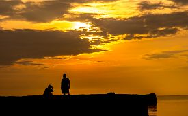 Silhouette of a man and women with sunset background.